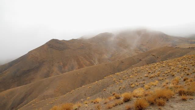 vidéos et rushes de ws view of fog rolling over atlas mountain top / marrakech, tensift, morocco  - maroc