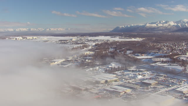 ws aerial view of fog with city and snow capped mountains / anchorage, alaska, united states - anchorage alaska stock videos & royalty-free footage