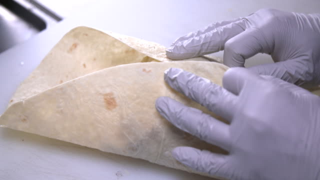 view of folding tortilla with hands - tortilla flatbread stock videos & royalty-free footage