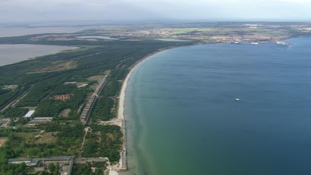 ws aerial view of following coastline with ocean / germany - küste stock-videos und b-roll-filmmaterial