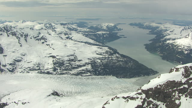 ws aerial pan view of foot of meares glacier at chugach mountains in prince william sound / alaska, united states - prince william sound stock videos and b-roll footage