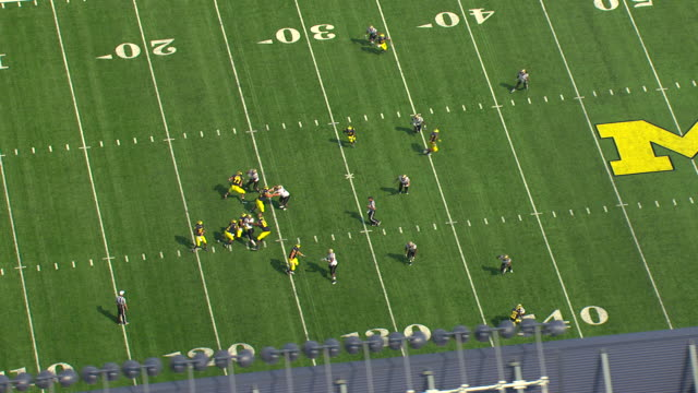 ms aerial zo view of football players on field at michigan stadium / ann arbor, michigan, united states - michigan stock videos & royalty-free footage