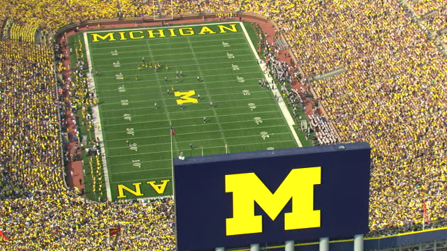 ms aerial zo view of football players on field at michigan stadium during game / ann arbor, michigan, united states - michigan stock videos & royalty-free footage