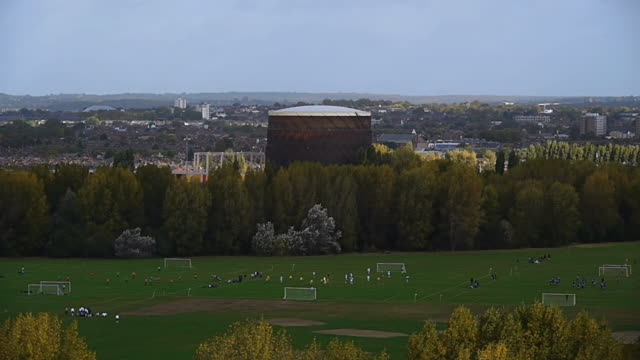 WS T/L View of Footballers play on Hackney Marshes against expansive backdrop of city / London, United Kingdom