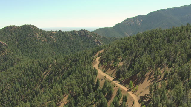 WS ZI AERIAL View of forest covered mountains with dust road ascending mountain / Colorado, United States