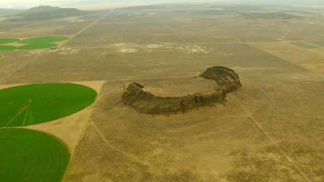 WS AERIAL View of Fort Rock volcanic rock formation next to crop irrigation circles / Oregon, United States
