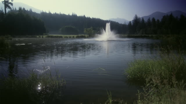 ws view of fountain in pond with mountain in background / squamish, british columbia, canada. - squamish stock videos & royalty-free footage