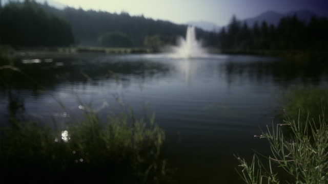 ws r/f view of fountain in pond with mountain in background / squamish, british columbia, canada. - squamish stock videos & royalty-free footage