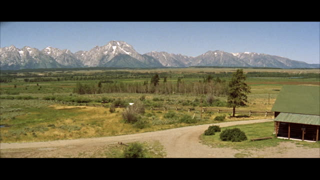td ms view of frame house on one sife of  gtand teton mountains  - grand teton stock-videos und b-roll-filmmaterial