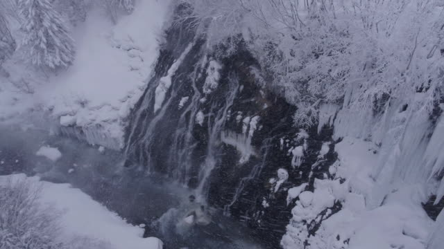 view of freezing shirahige falls and snow-coverd mountains in biei, hokkaido, japan - crag stock videos and b-roll footage