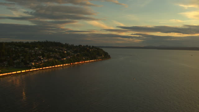 WS AERIAL View of freight train moving along coast at sunset / Washington, United States