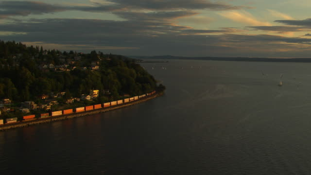 WS AERIAL ZI View of freight train moving along coast at sunset / Washington, United States