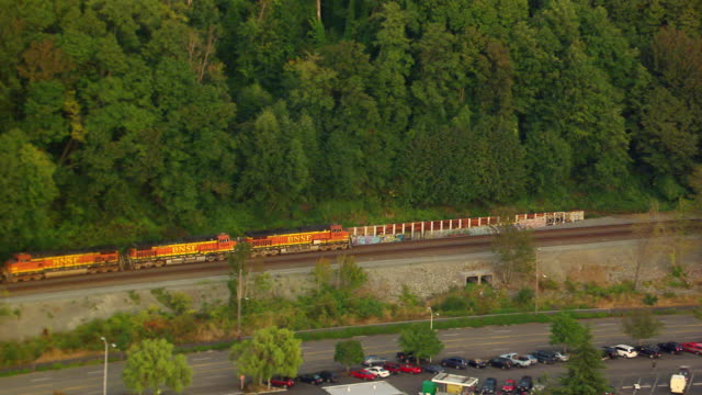 WS AERIAL ZI View of freight train moving through Seattle suburbs / Washington, United States