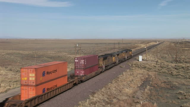 view of freight train passing through rural area in wyoming united states - c119gs stock videos & royalty-free footage