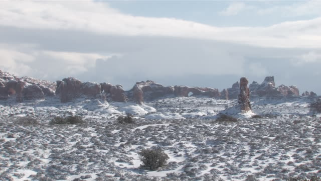 ms zo view of fresh snow on red rock desert, natural arch / moab, utah, united states - moab utah stock videos & royalty-free footage