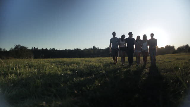 WS PAN View of friends walking in field at sunset / Langley, British Columbia, Canada