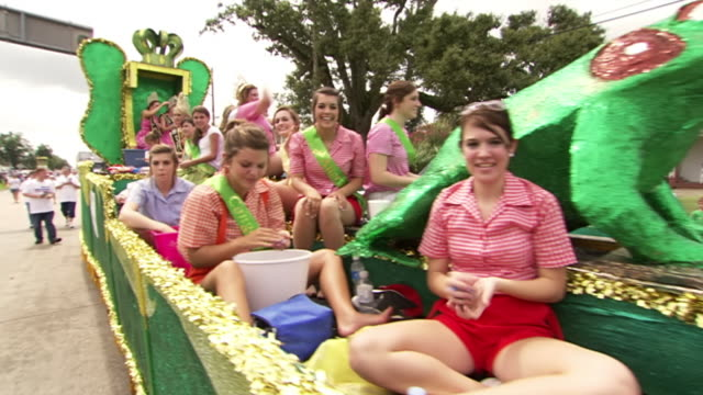 ws pov view of frog derby queen contestants parade on float and throwing candy at audience during rayne frog festival / rayne, louisiana, united states - beauty contest stock videos & royalty-free footage