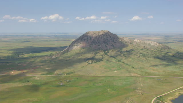 ws aerial tu view of from lake at base to reveal bear butte in meade county with clouds casting shadows on mountain / south dakota, united states - butte rocky outcrop stock videos & royalty-free footage
