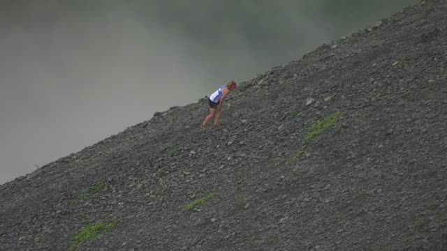 WS AERIAL View of front runner climbs bare mountain during Mount Marathon Race / Seward, Alaska, United States