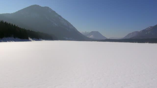ws aerial view of frozen lake sylvensteinspeicher in winter / alpine mountains, bavaria, germany - ruhige szene stock-videos und b-roll-filmmaterial