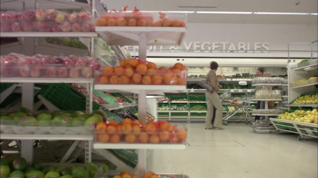 ms pan view of fruit and vegetable isle in supermarket with shoppers walking in background / north finchley, london, uk - four in a row stock videos & royalty-free footage