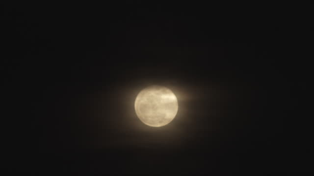 ws t/l view of full moon at night behind clouds / orem, utah, usa - orem video stock e b–roll