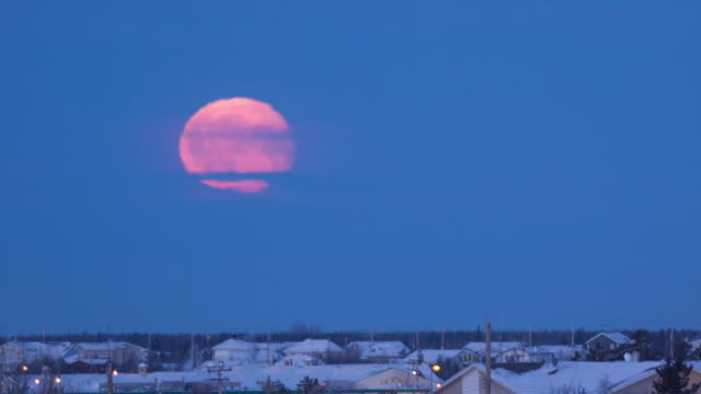 WS T/L View of full moon setting over downtown covering with snow / Yellowknife, Northwest Territories, Canada