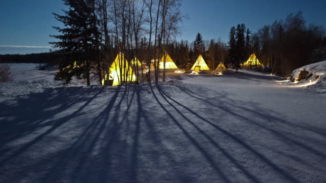 ws t/l view of full moon setting over teepees above snow covering forest / yellowknife, northwest territories, canada - tent stock videos & royalty-free footage