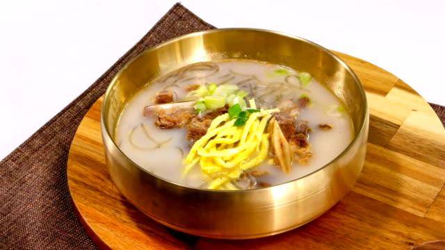 view of galbitang (beef short ribs soup) with  jidan (egg garnish) on top (famous korean traditional dish) - garnish stock videos & royalty-free footage