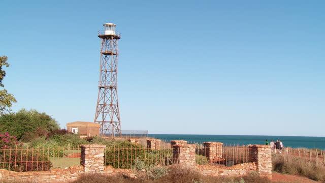 ws pan view of gantheaume point lighthouse while people in background / broome, western australia, australia - gemeinsam gehen stock-videos und b-roll-filmmaterial