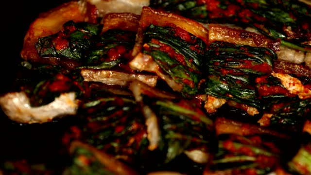 view of gat (leaf mustard) kimchi (popular traditional side dish in korea) on top of the grilling pork belly - mustard stock videos and b-roll footage