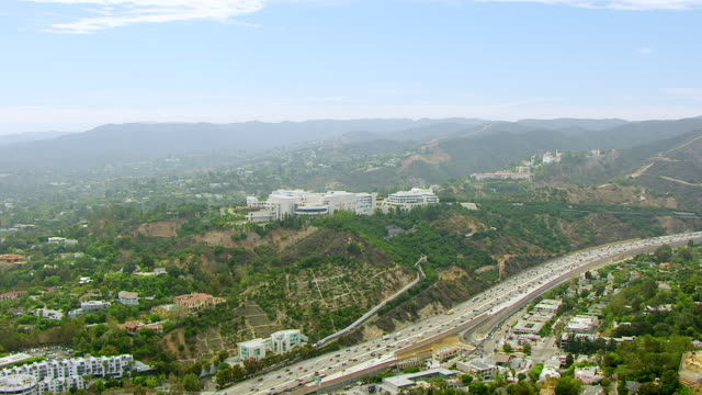 ws aerial pov view of getty center with traffic in foreground / los angeles, california, united states - brentwood los angeles stock videos & royalty-free footage