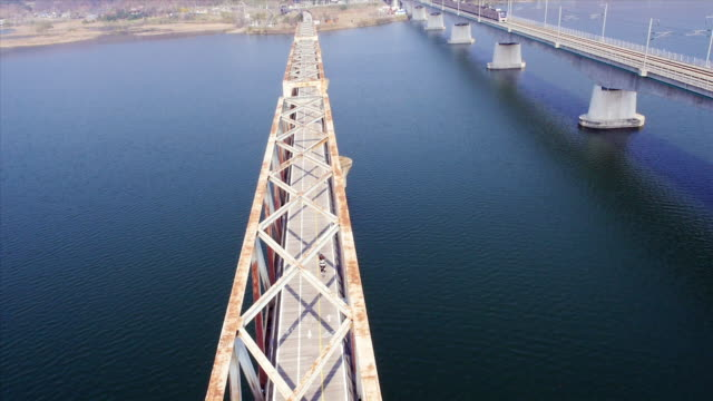 ws aerial zi view of girl cycling on bridge of namhan river with train passing on another railway bridge / yangpyeong, gyeonggi-do, south korea - nur weibliche teenager stock-videos und b-roll-filmmaterial