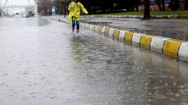 slow mot - view of girl running through water puddle - raincoat stock videos & royalty-free footage