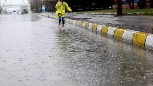 vídeos de stock, filmes e b-roll de mot lento - vista da menina correndo pela poça de água - capa de chuva