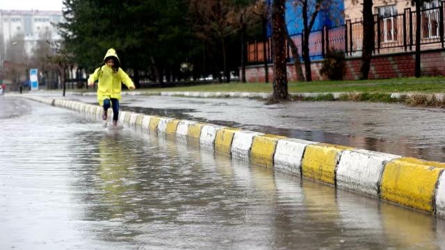 Blick auf Mädchen laufen durch Wasser Pfütze