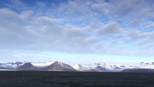 vídeos de stock e filmes b-roll de ws pan view of glaciers and snow covered mountain and road / iceland - 1 minuto ou mais