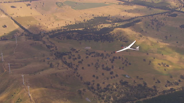 ws aerial zi view of glider plane and windmills / macarthur, victoria, australia - glider stock videos & royalty-free footage