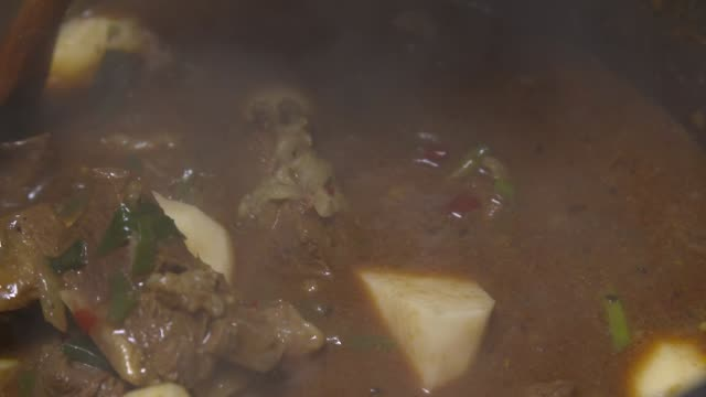 View of Goat Meat Curry(Jamaican food) being stirred with spatula