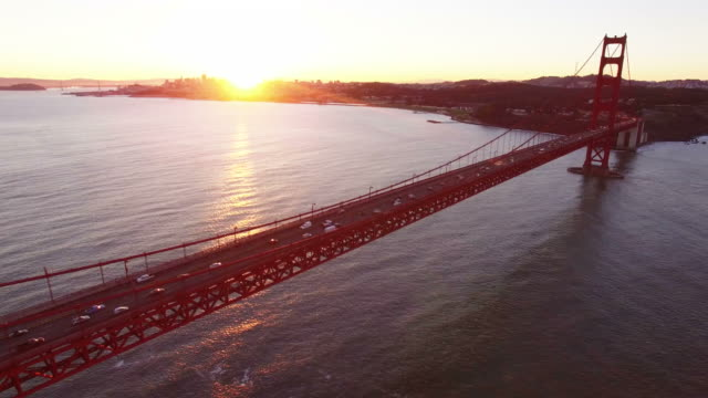 View of Golden Gate Bridge with sunlight and traffic at sunrise