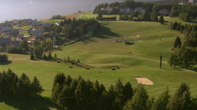 ws aerial view of golf course crans montana within village / crans montana, valais, switzerland - campo da golf video stock e b–roll
