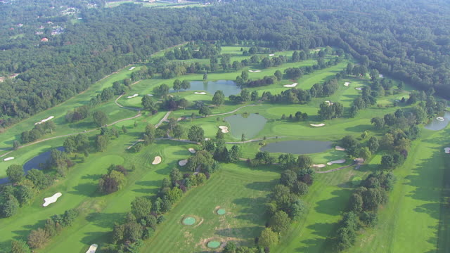 ws aerial view of golf course surrounded by trees / new york, united states - golf course stock videos and b-roll footage