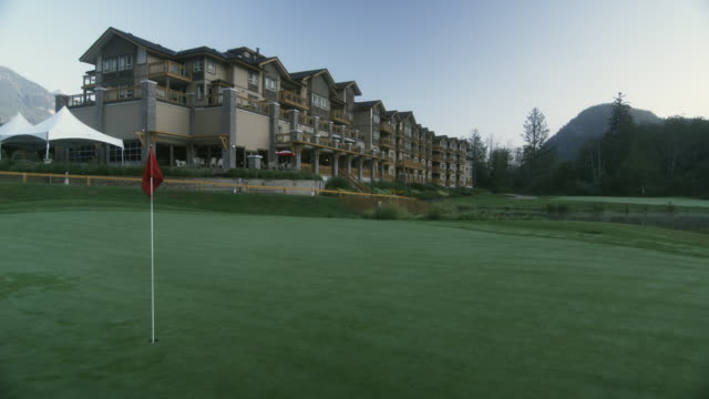 ws view of golf course with golf flag, hotel suite in background / squamish, british columbia, canada. - golf flag stock videos & royalty-free footage