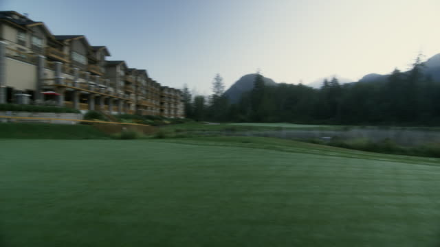 ws pan view of golf course with golf flag, hotel suite in background / squamish, british columbia, canada. - golf flag stock videos and b-roll footage