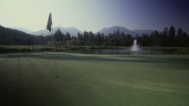 ws view of golf course with golf flag, mountain in background / squamish, british columbia, canada. - golf flag stock videos and b-roll footage
