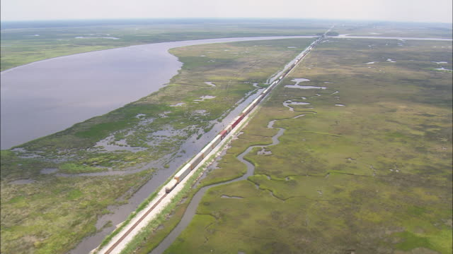 ws aerial view of goods train passing through railway bridge / louisiana, united states - railway bridge stock videos & royalty-free footage