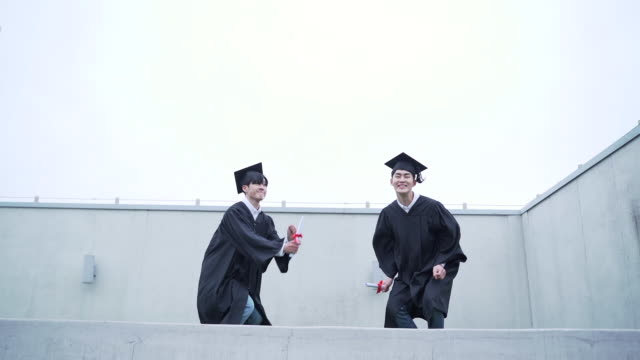 view of graduates jumping in a row - east asian ethnicity stock videos & royalty-free footage