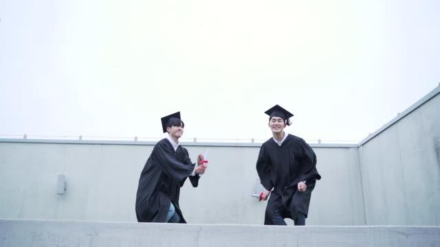 vídeos y material grabado en eventos de stock de view of graduates jumping in a row - coreano oriental