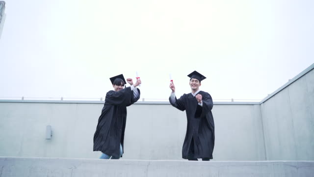 stockvideo's en b-roll-footage met view of graduates jumping in a row - diploma