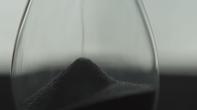 View of grains of sand falling down and stacking in a sandglass